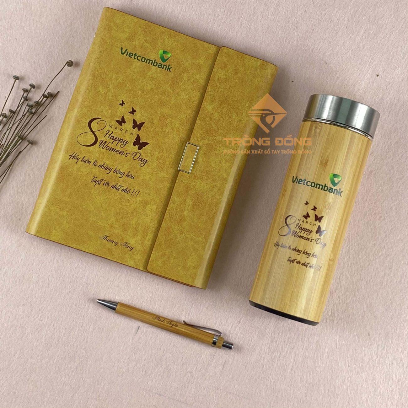 Bộ Giftset 8/3 gồm 3 món gồm sổ tay bìa da, bình giữ nhiệt và bút gỗ in logo NH Vietcombank.